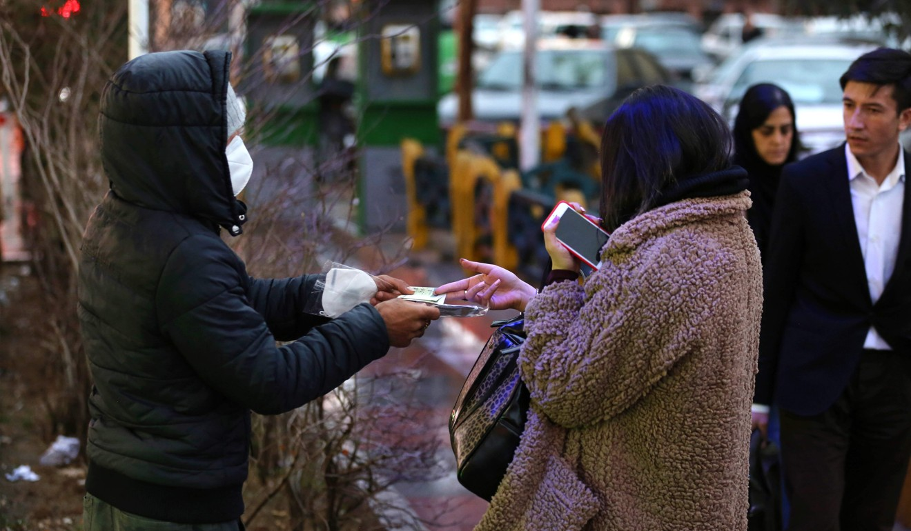 A woman buys a face mask from a street vendor in Tehran on Thursday. Iran reported its first cases of the virus on February 13. Photo: AFP