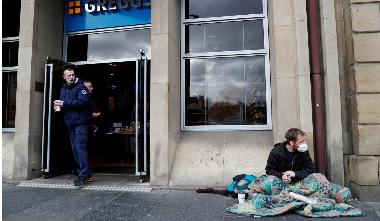A homeless man wearing a protective face mask sits outside a bakery in Newcastle, UK, as another man looks on. Photo: Reuters