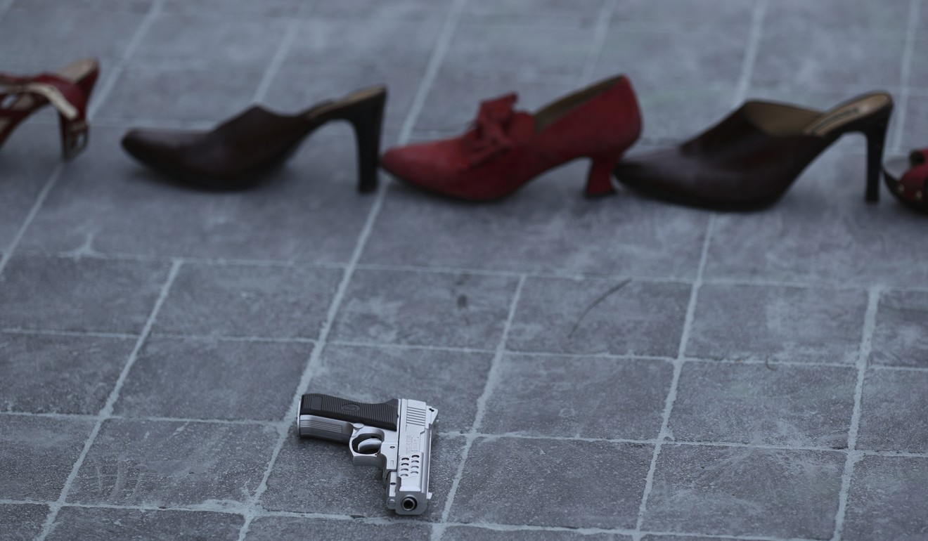 A toy gun in front of a line of red shoes representing murdered women as part of a performance during the International Women's Day strike in Mexico this month. Photo: AP