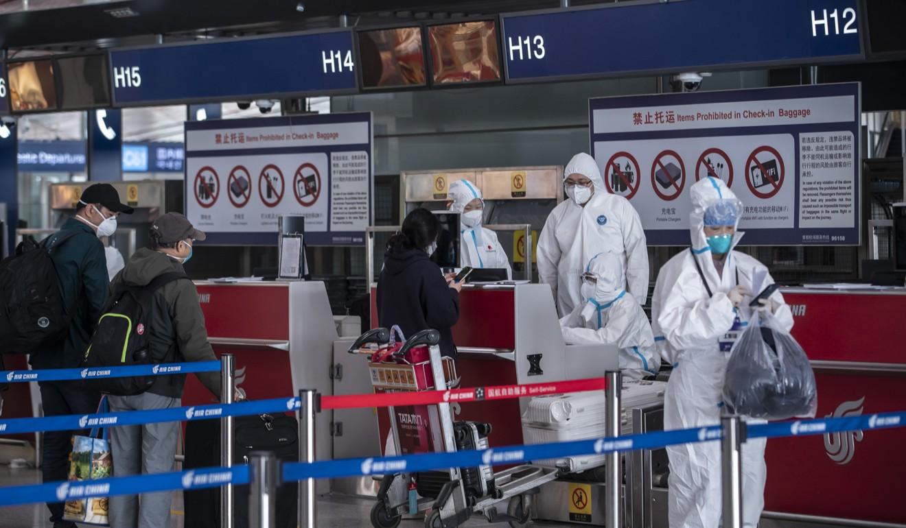 Funcionários do aeroporto em trajes de proteção no Aeroporto Capital de Pequim.  Foto: Bloomberg
