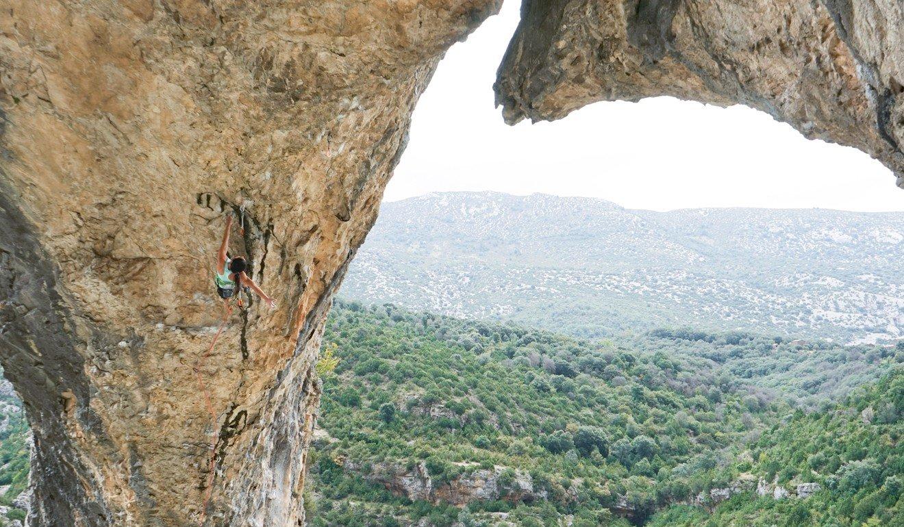 Alannah Yip scales a big rock during an outdoor climbing expedition. Photo: JJ Mah