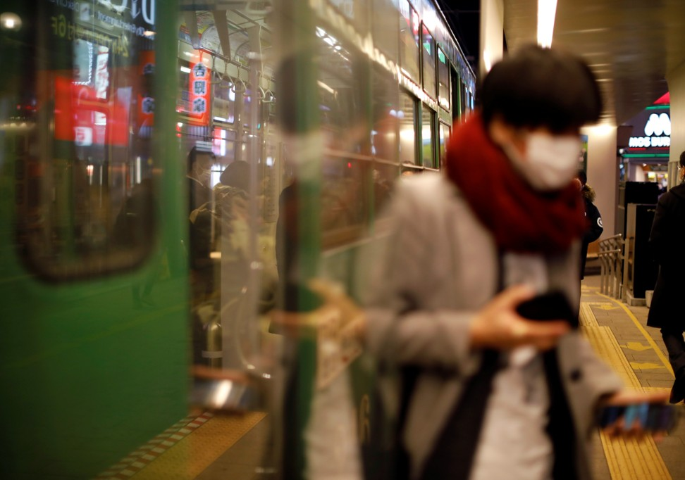 A passenger wearing a protective face mask alights from a tram in Sapporo, Hokkaido, on February 25, 2020. Photo: Reuters