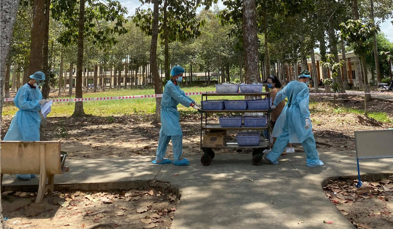 Staff in protective clothing deliver food in a quarantine camp in Dong Thap Province in Vietnam's Mekong Delta. Photo: Phuong Chinh