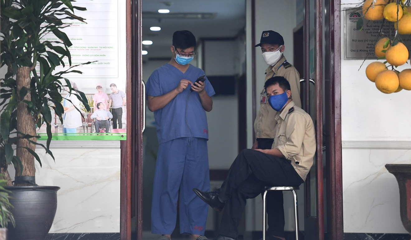 A medical staff member and security guards wearing face masks stand at the entrance of a private hospital under quarantine following a visit by a Vietnamese woman who arrived from London and later tested positive for coronavirus. Photo: AFP