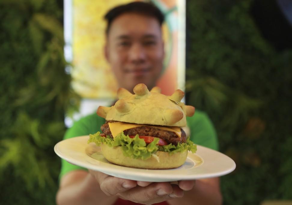 Restaurant owner Hoang Tung holds up a corona burger. Photo: AP