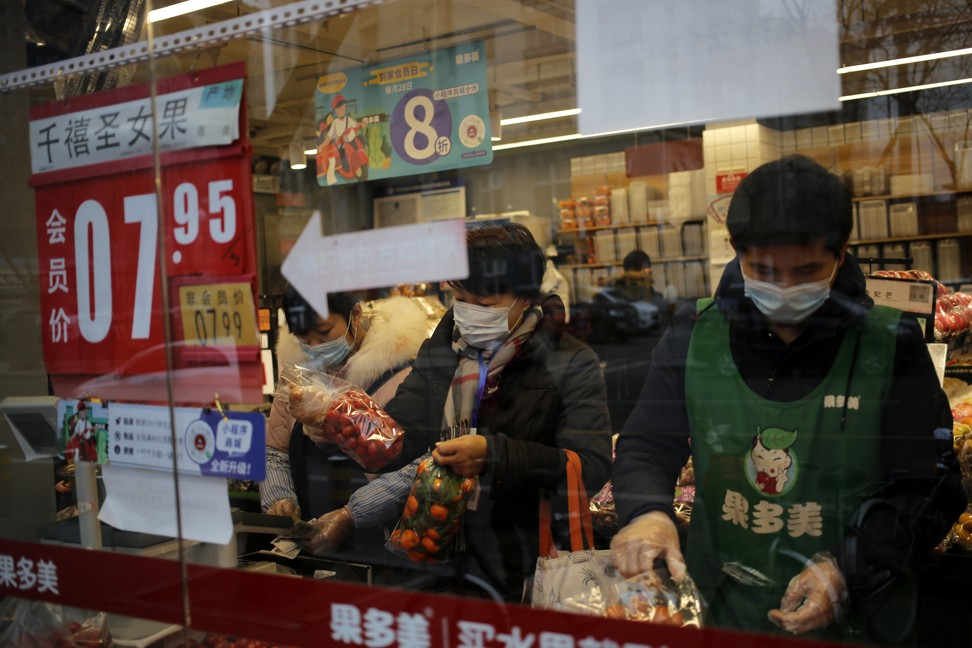 People wearing masks buy vegetables at a store in Beijing. Photo: EPA-EFE