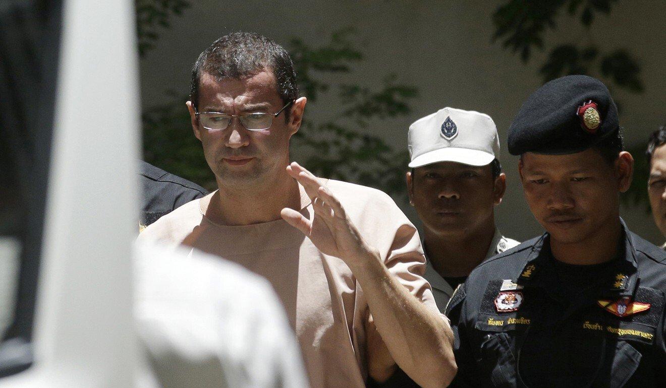 Xavier Justo es escoltado por oficiales de correccionales tailandeses cuando sale de un tribunal en Bangkok.  Sirvió más de un año en una prisión tailandesa después de ser condenado por chantaje vinculado al escándalo de 1MDB.  Foto: AP