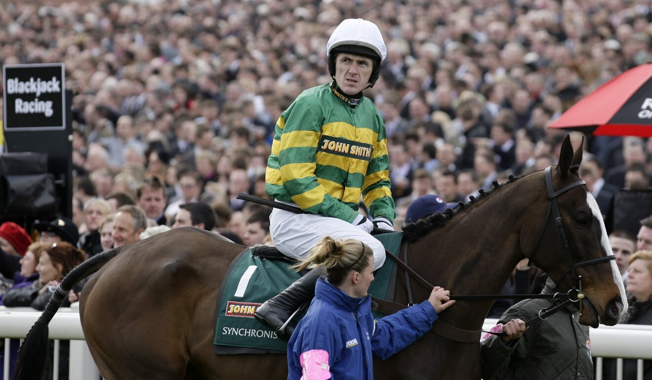 Jockey Tony McCoy is led to the start of the 2012 Grand National in front of a packed crowd. Photo: AP