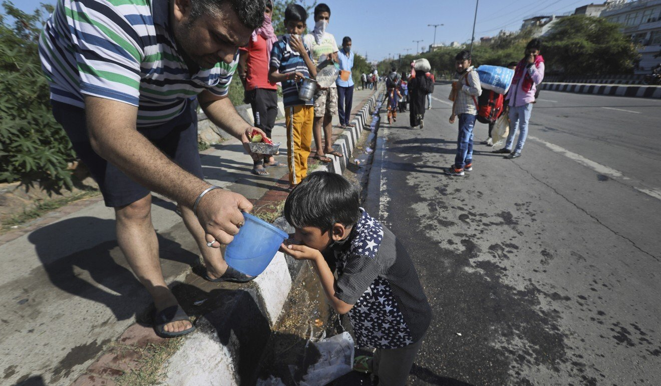 A man offers water to a child of a migrant labourer in New Delhi, as his family returns to their village due to the coronavirus lockdown. Photo: AP
