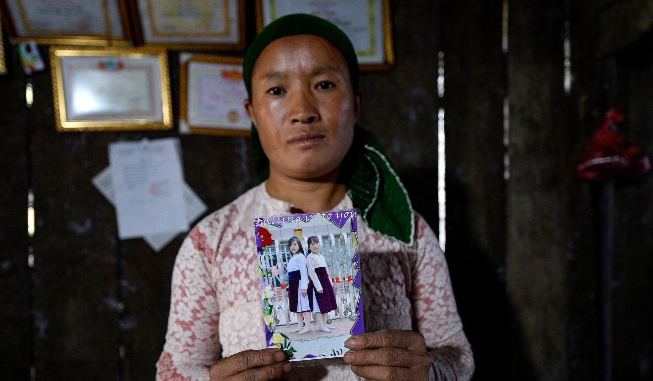 A Vietnamese mother in Ha Giang with a photograph of her missing teenage daughter Dua, who is thought to have been sold as a child bride. Photo: AFP