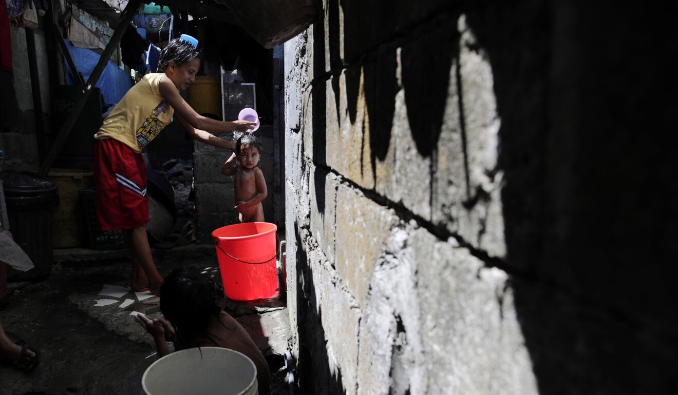 A mother bathes her child in a slum area of Quezon City in the Philippines. Photo: EPA
