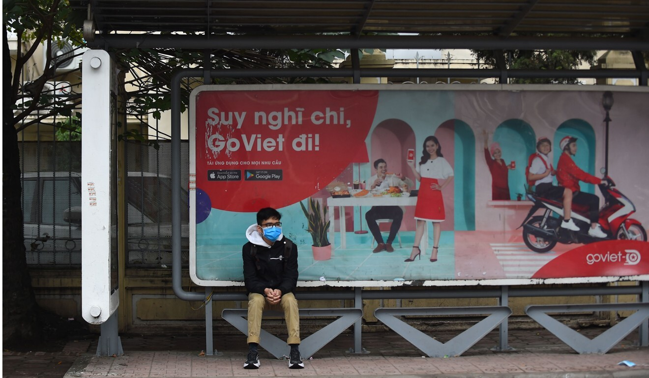 A teenager at a bus stop in Hanoi wears a mask amid the coronavirus outbreak. Photo: AFP