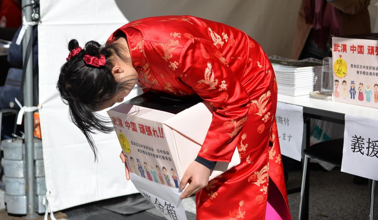 A woman in Tokyo collects donations in early February to help those in China affected by coronavirus. Photo: Xinhua