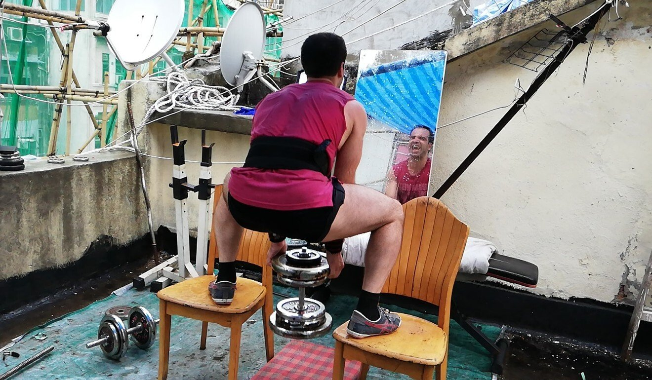 Unable to afford a gym, Alex Tyronne works out on his roof with makeshift equipment.