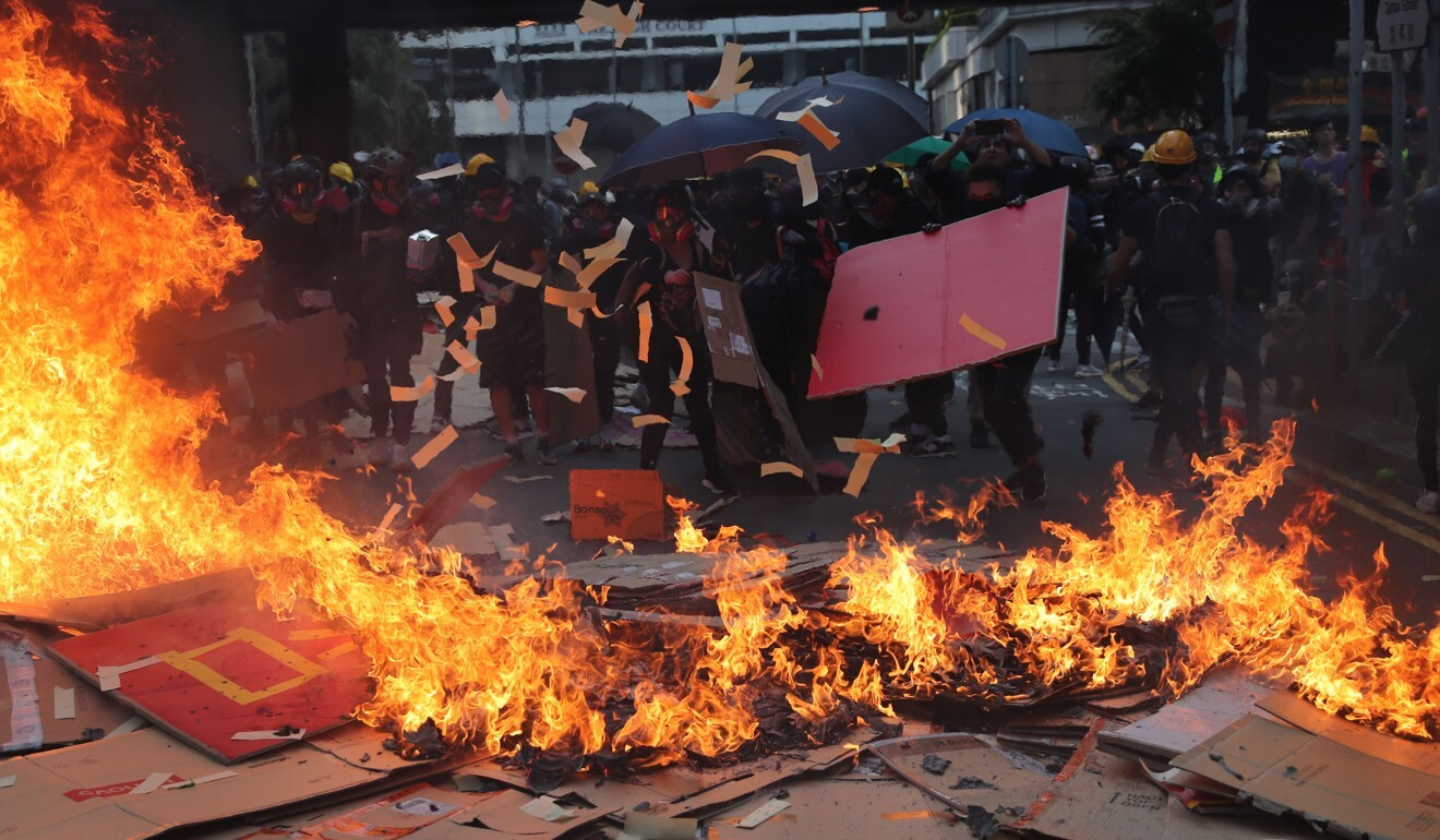 Protesters set fire and toss paper offerings in Admiralty on National Day last year. Photo: Sam Tsang