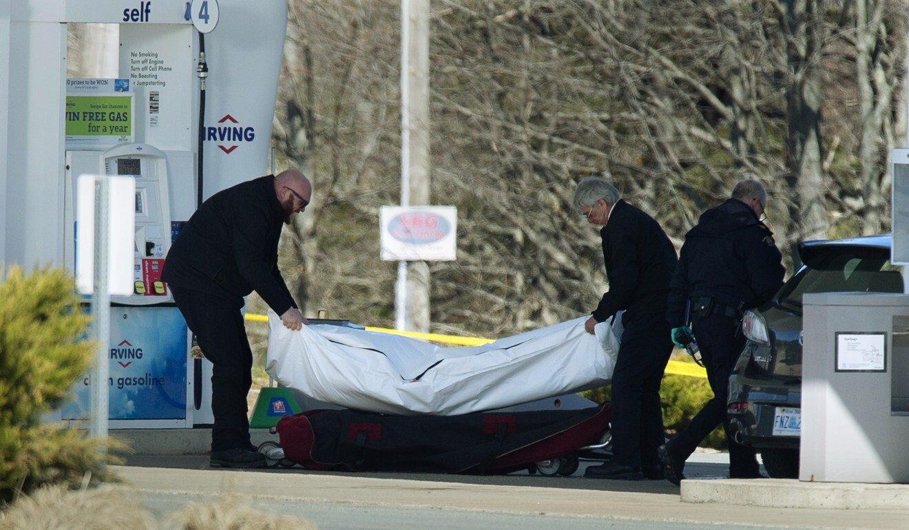 Workers with the medical examiner's office remove a body from petrol station in Enfield, Nova Scotia. Photo: AP