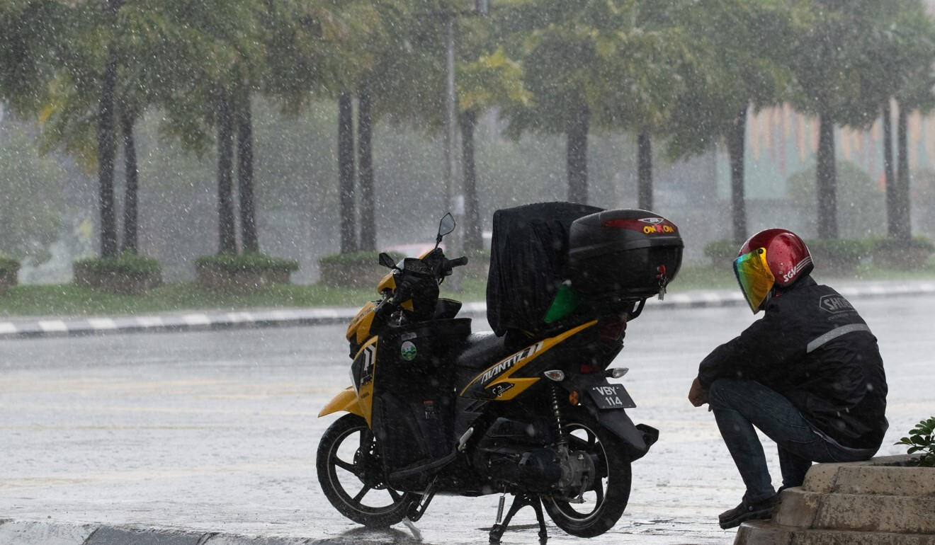 A food delivery rider takes shelter under a bridge in Malaysia, April 6, 2020. Photo: AFP