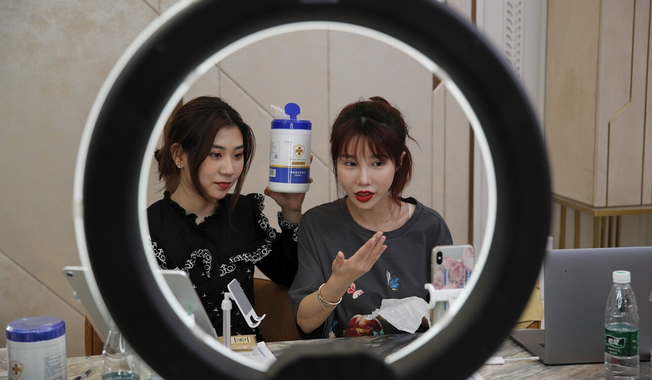 In this May 5 photo, online celebrity Zhang Mofan, right, introduces disinfectant wipes to her online fans via live-streaming at her flat in Beijing. Photo: AP