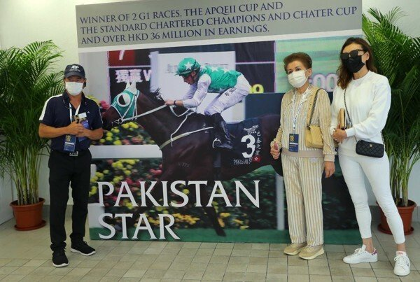 Tony Cruz, Kerm Din's wife and Paulene Cruz stand in front of a poster of Pakistan Star.