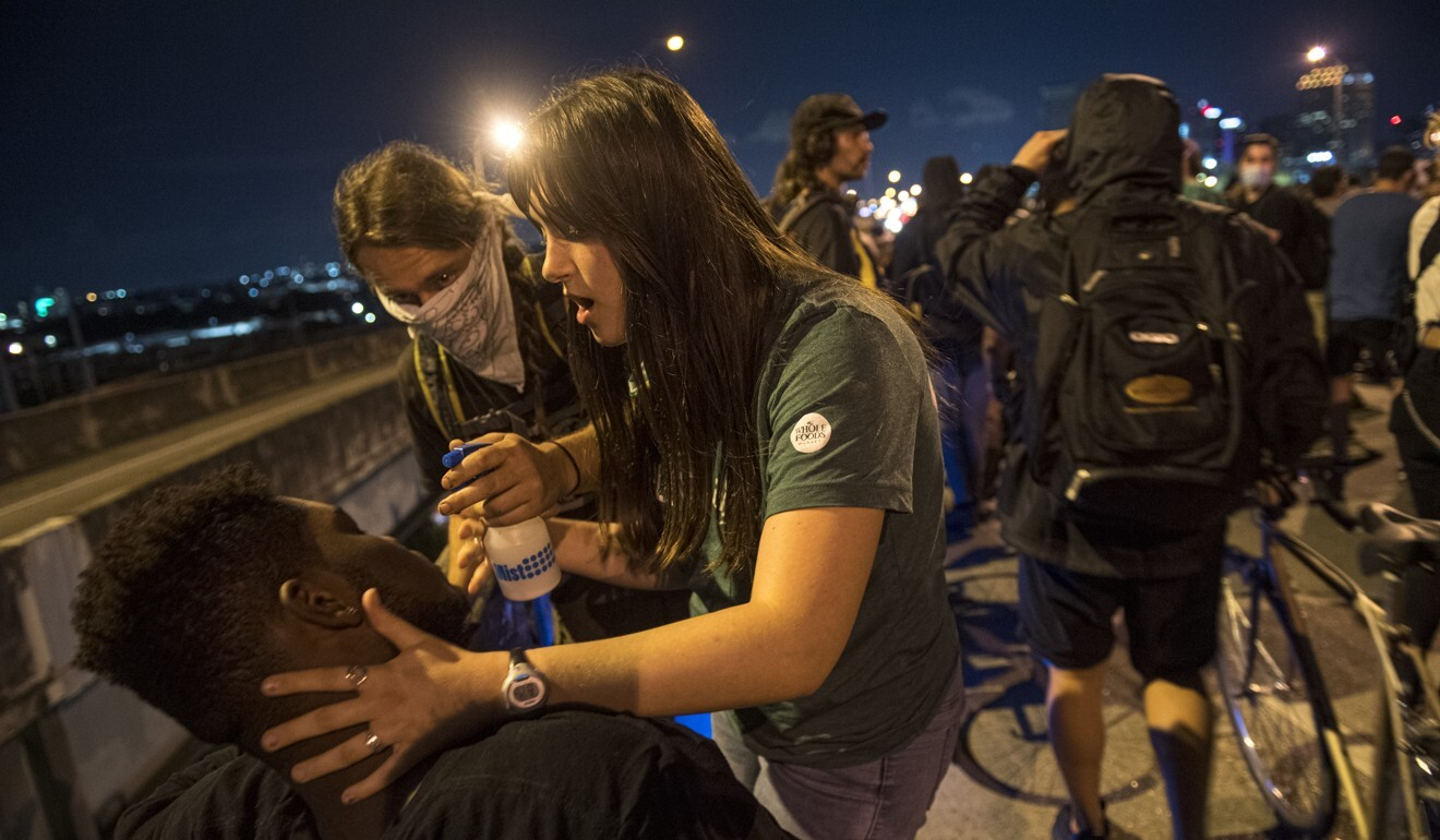 Protesters help others who have been affected by tear gas fired by New Orleans police. Photo: AP