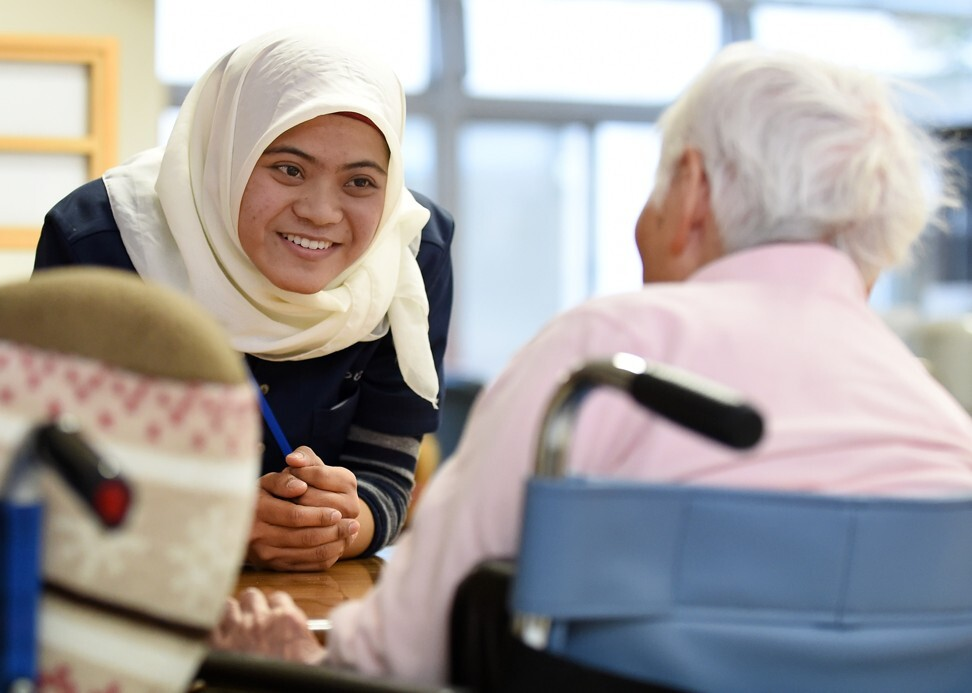 A nurse talking to a woman at a nursing home in Tokyo. The number of care workers in Japan stood at about 1.95 million in 2017. Photo: AFP