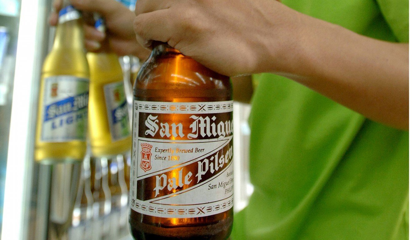 A customer buys San Miguel beers at a store in Manila. The businessman who led the food and drink empire has died at the age of 85. Photo: AFP