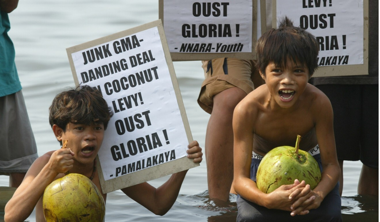 Philippine children hold coconuts during a 2003 protest over plans by the government then led by Gloria Macapagal Arroyo to propose out-of-court deals on the disputed coconut levy fund with tycoon Eduardo Cojuangco. Photo: Reuters