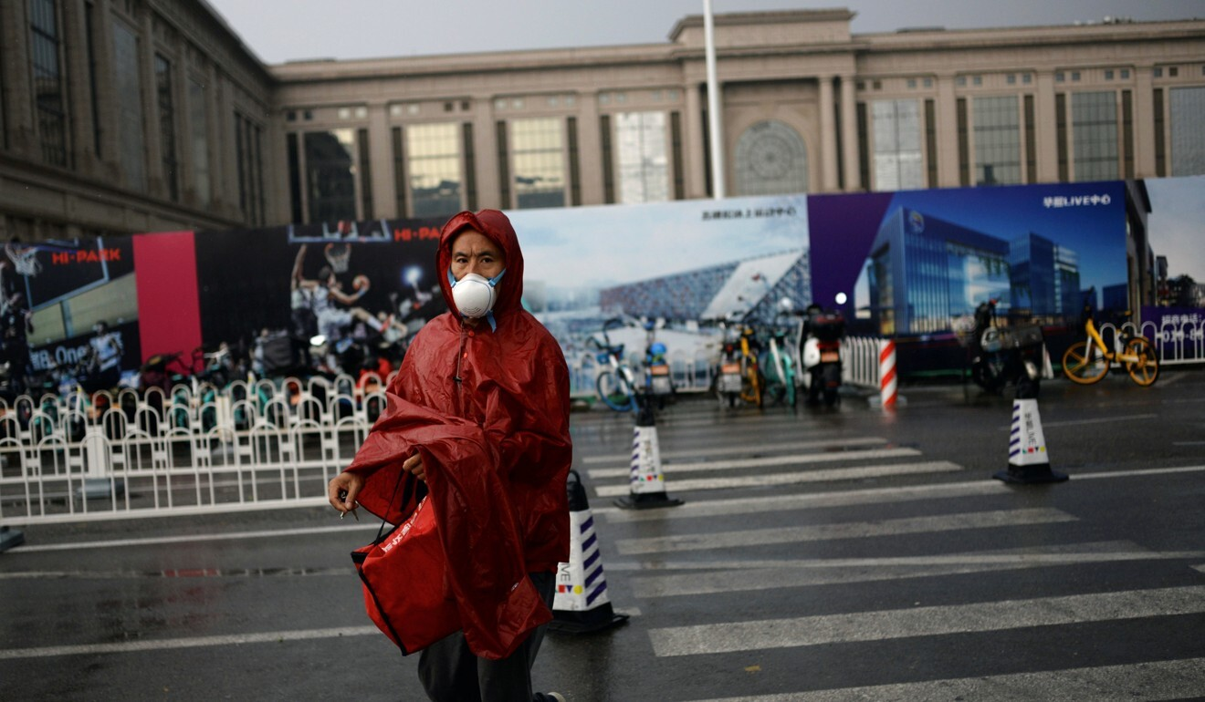 A man wearing a face mask crosses a road near a shopping complex in Beijing, where there has been a new outbreak of Covid-19. Photo: Reuters