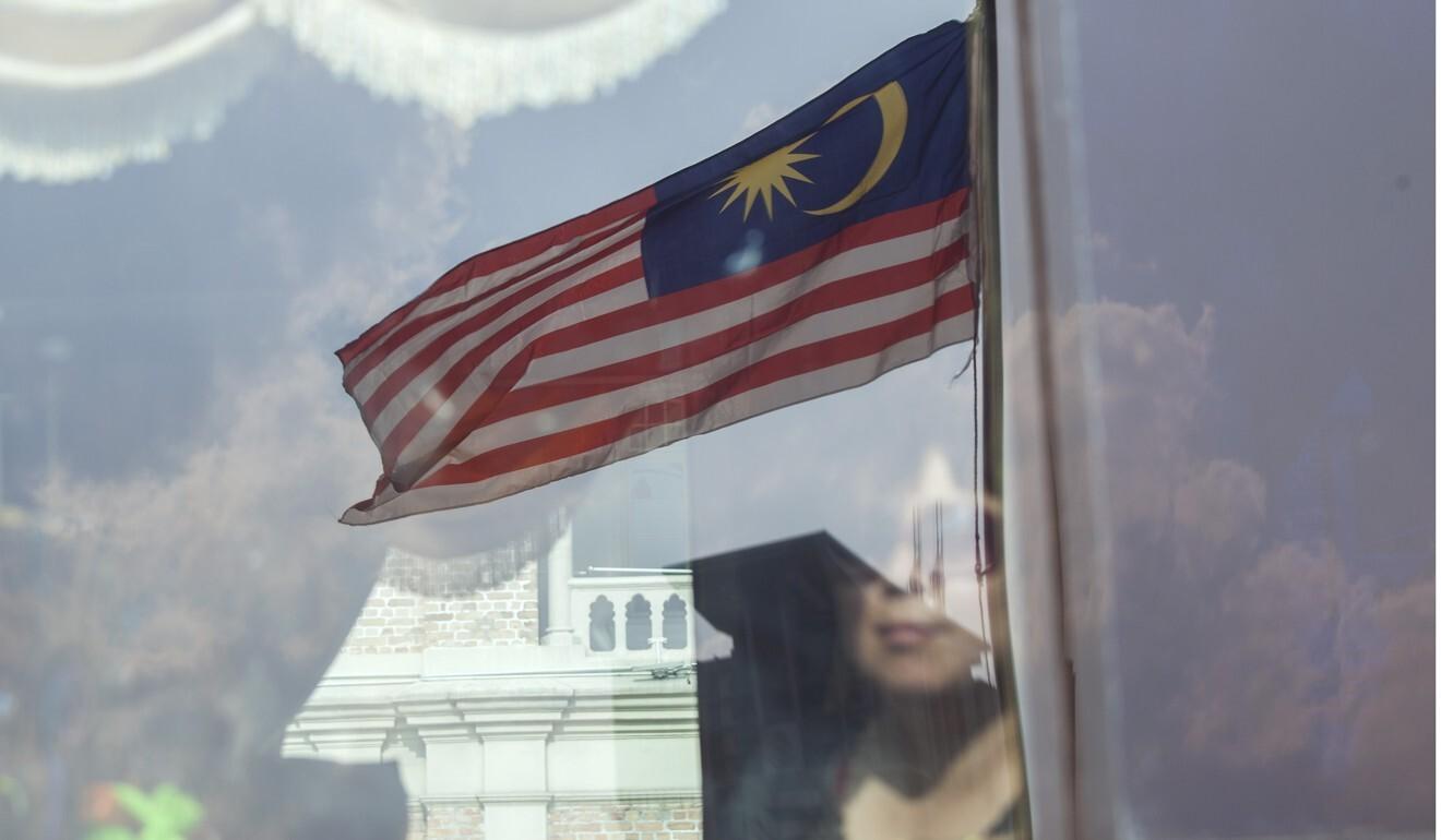 A Malaysian flag is reflected on bus window in Kuala Lumpur. Photo: Bloomberg