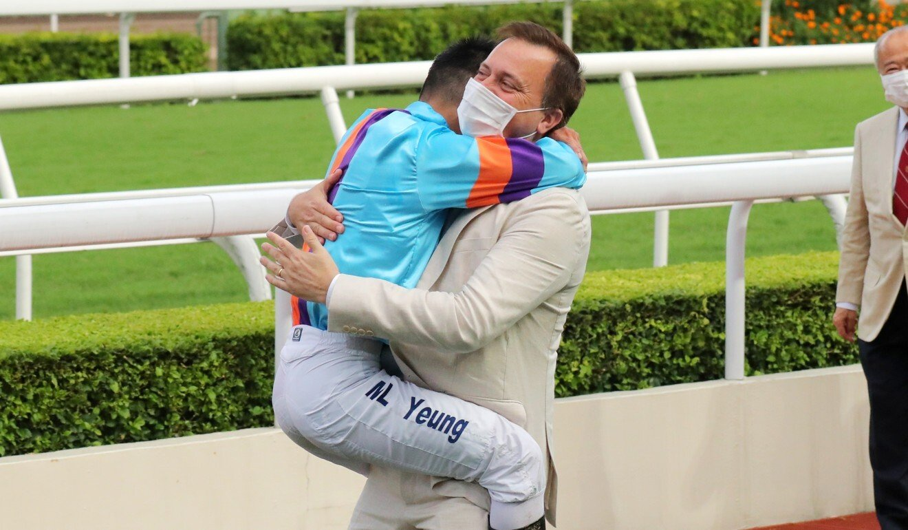 Jockey Keith Yeung and trainer Caspar Fownes embrace after Dances with Dragon's victory.