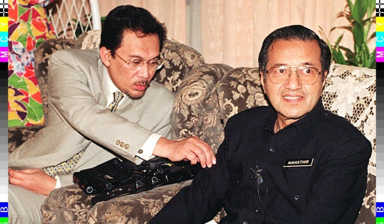 Anwar, at the time the deputy prime minister, removes a dustball from then prime minister Mahathir's sleeve during a press conference in 1997. Photo: AFP