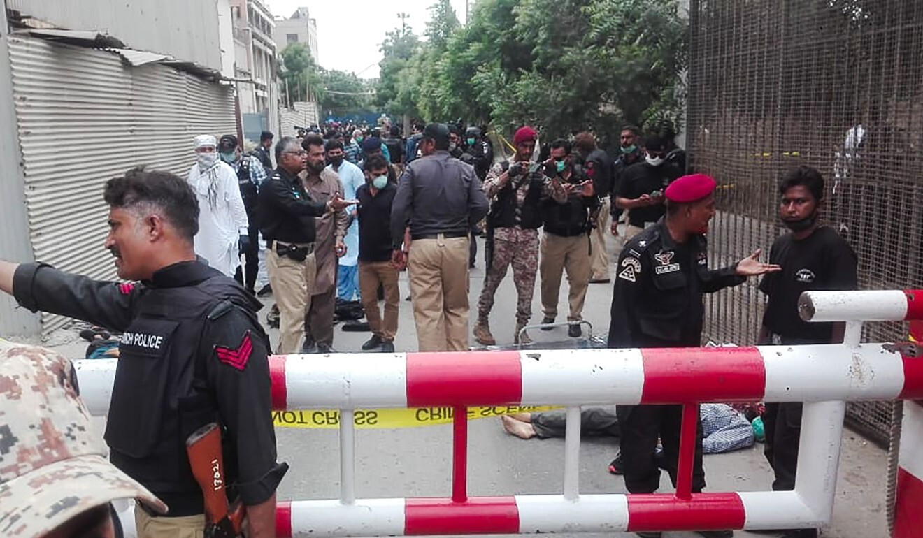 Policemen secure an area around a body outside the Pakistan Stock Exchange building on June 29. Photo: AFP