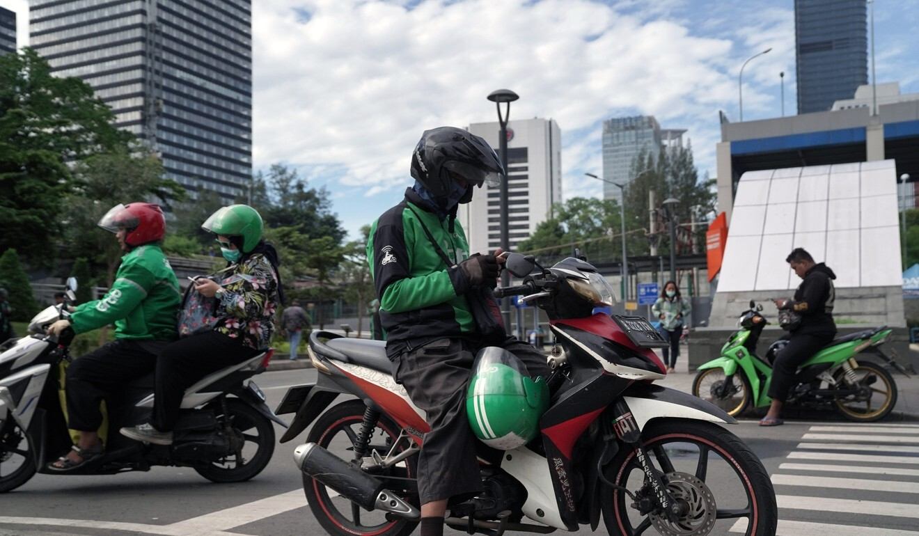 Gojek drivers sit on their motorcycles along a street in Jakarta, Indonesia, on Wednesday, April 1, 2020. Photo: Bloomberg