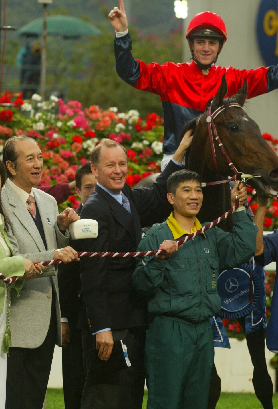 John Moore celebrates Viva Pataca's win in the 2006 Hong Kong Derby with jockey Christophe Soumillon and owner Stanley Ho (left).