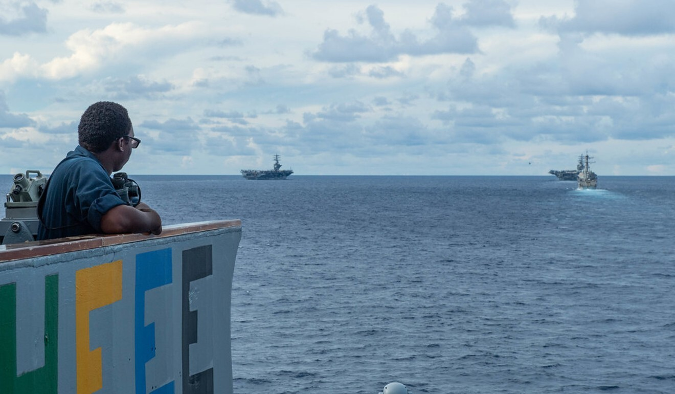 Boatswain's mate Seaman Clarkensy Smith looks on from the USS Antietam as the USS Nimitz, USS Ronald Reagan and USS Mustin steam in formation. Photo: US Navy