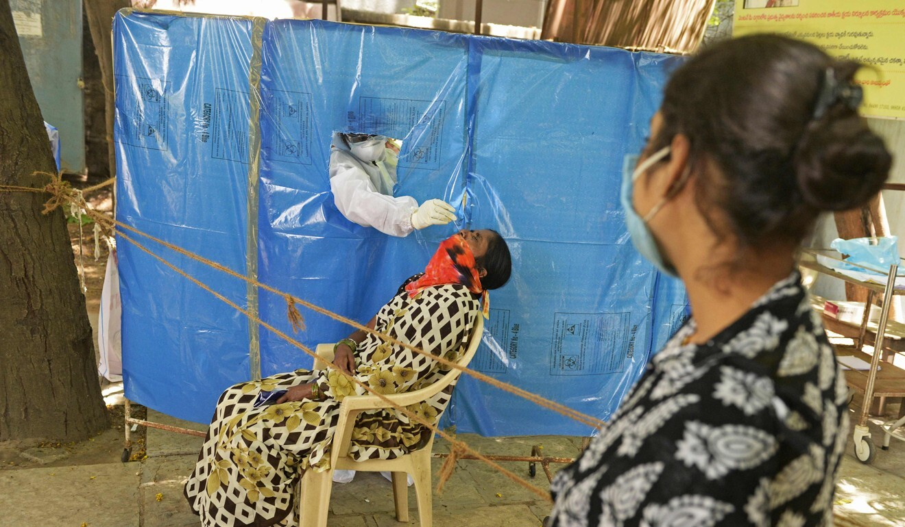 A health worker wearing collects a swab sample at a free testing centre in Hyderabad, India. Photo: AFP