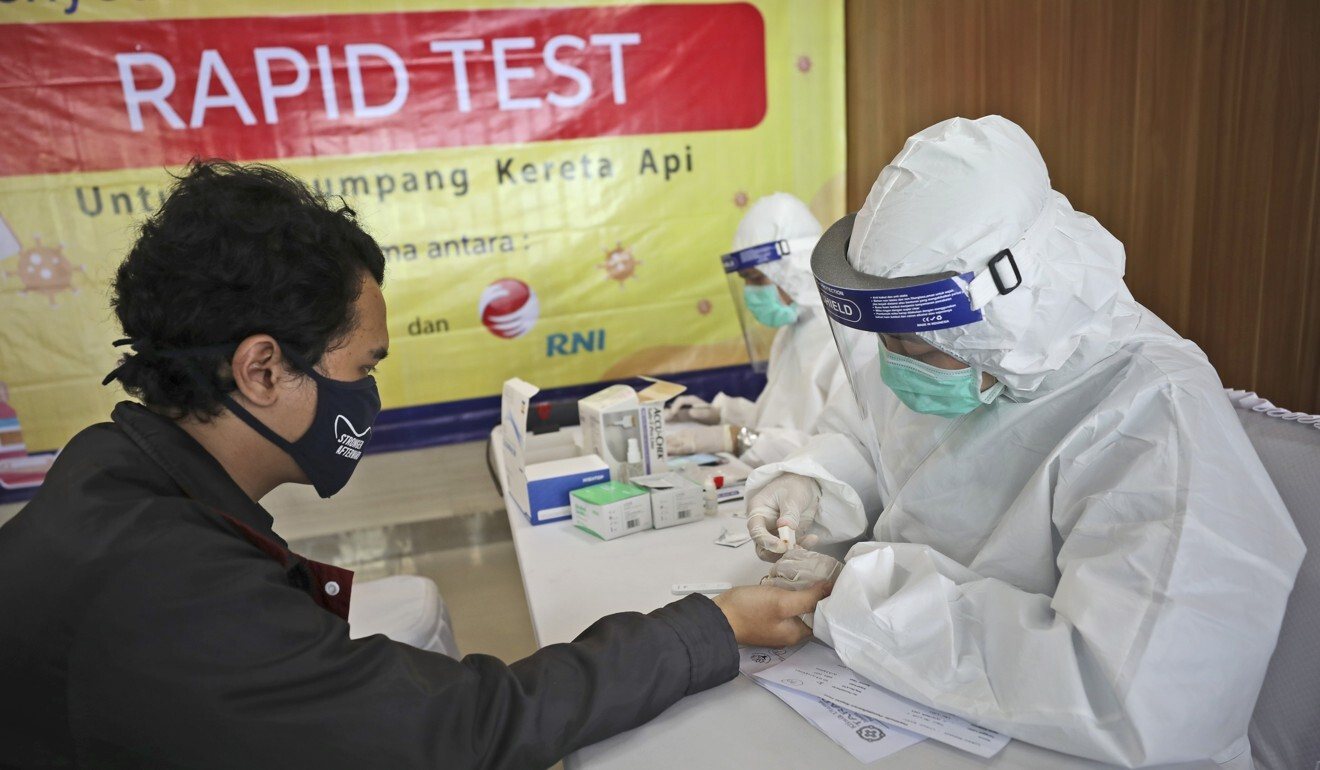 A health worker takes a blood sample from a long-distance train passenger in Jakarta, Indonesia. Photo: AP