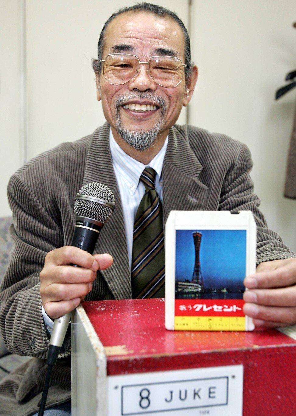 Inoue displays the Juke 8 karaoke machine and its music cartridge at his office in Nishinomiya city near Osaka, Japan in 2004. Photo: AFP