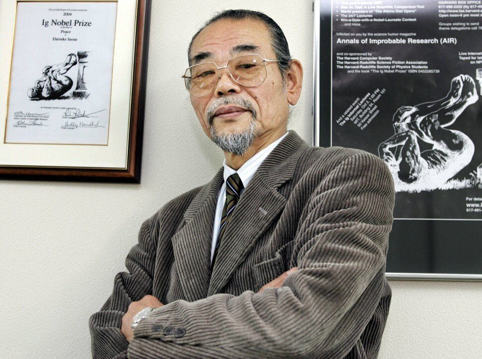 At his office in Nishinomiya, Inoue stands beside the 2004 Ig Nobel Prize he was awarded for inventing karaoke. Photo: AFP