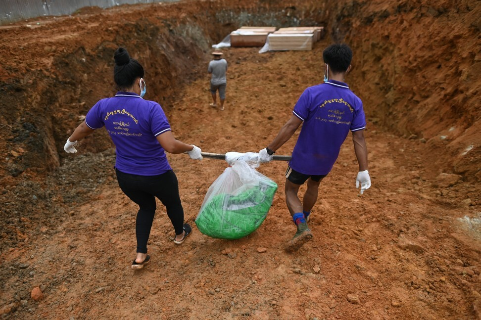 Volunteers carry a bag holding the partial remains of a miner to be buried in a mass grave, one of hundreds who died in the July 2 landslide in Hpakant. Photo: AFP