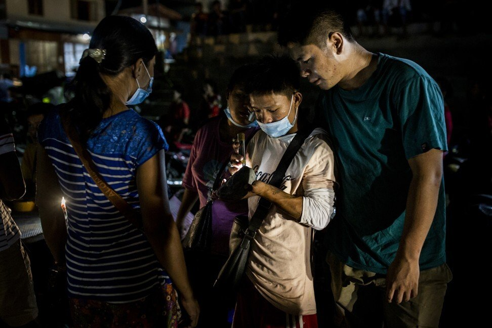 A buyer inspects jade being sold in a market in Hpakant. Photo: Hkun Lat