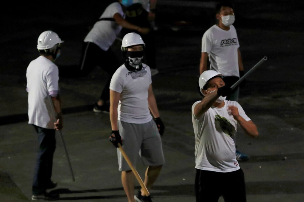 Men in white T-shirts with poles seen in Yuen Long after attacking anti-extradition bill demonstrators at a railway station. Photo: Reuters