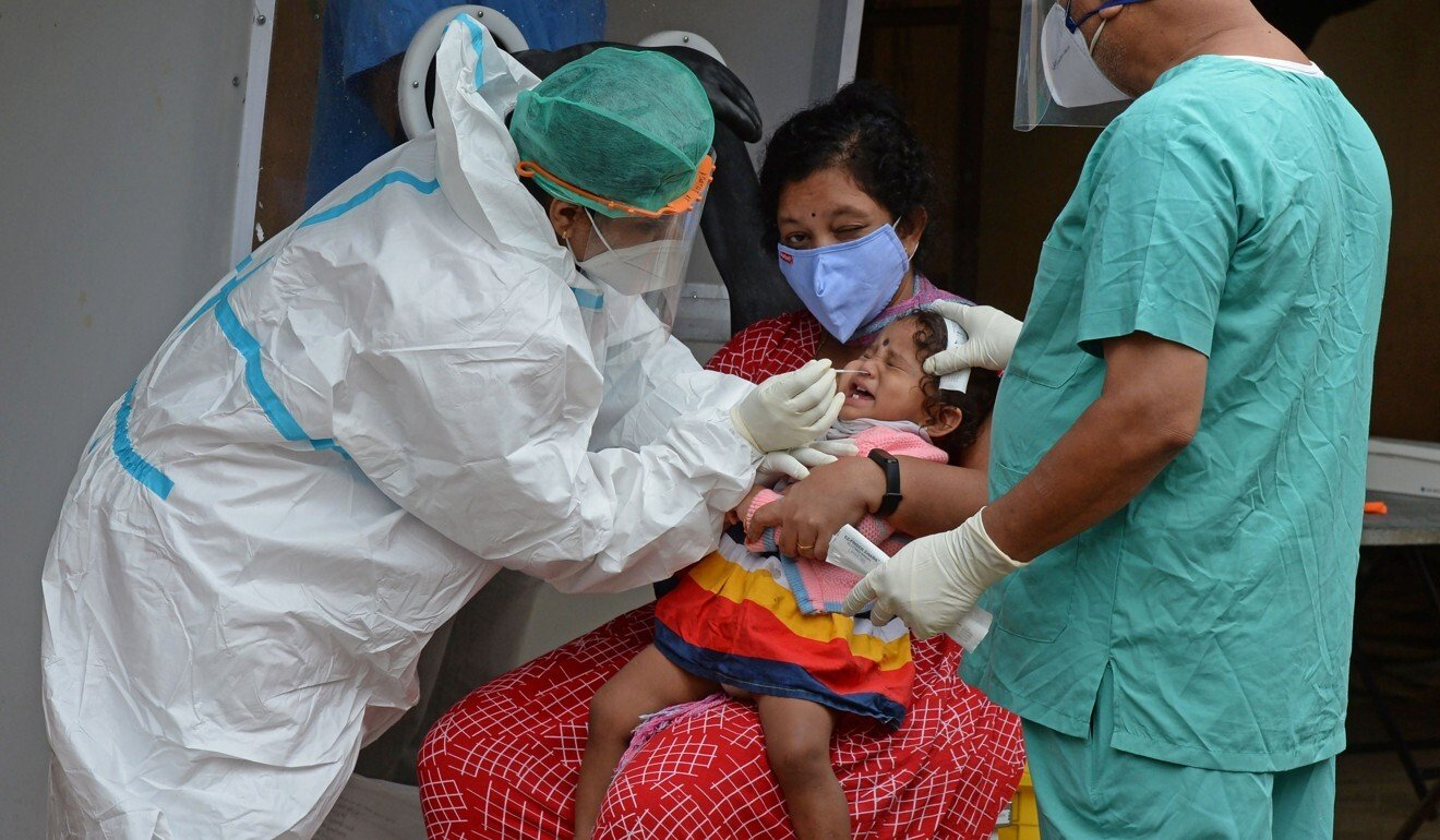 A health worker wearing PPE collects a swab sample from a child at a free Covid-19 testing centre in Hyderabad. Photo: AFP