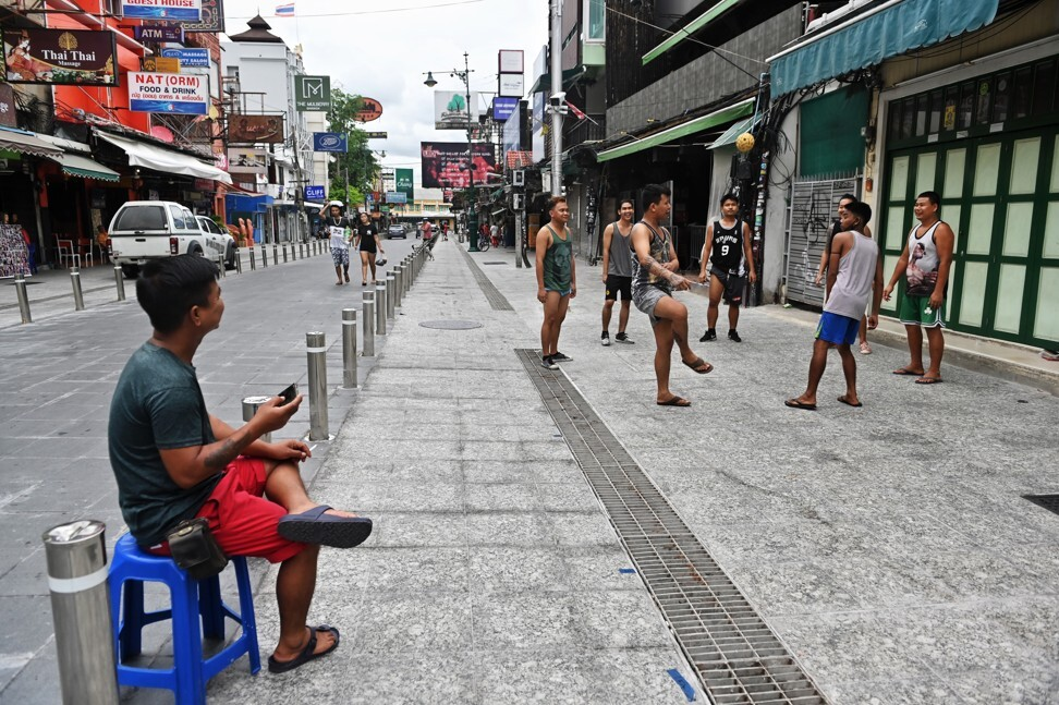 Vendors and bar staff from Myanmar play chinlone as they wait for customers at Khao San Road in Bangkok. The popular tourist district has been empty due to travel restrictions on travellers entering Thailand during the coronavirus. Photo: AFP