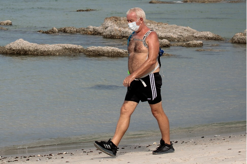 A man wearing a face mask to prevent the spread of coronavirus walks along Hua Hin beach in Thailand. Photo: AFP