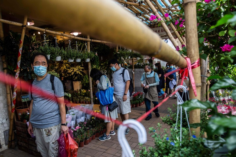 People walk through a flower market in Hong Kong on August 16. Double-digit inflation is a thing of the past, according to the data. But does anyone believe their costs rise by just 4 per cent a year? Photo: AFP