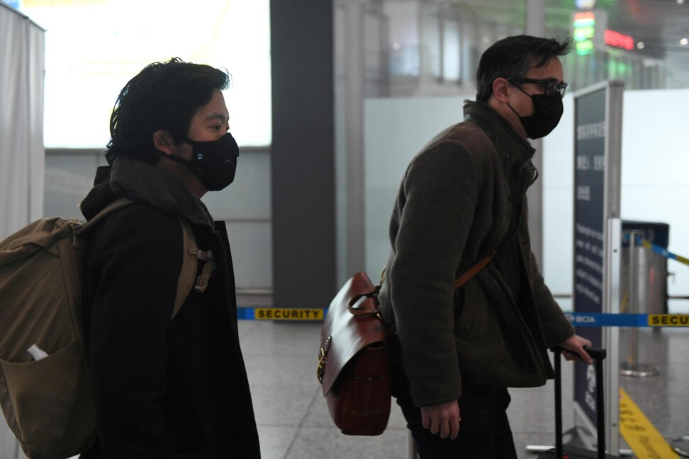 Wall Street Journal reporters Josh Chin, right, and Philip Wen walk through Beijing Capital Airport before their departure on February 24, 2020 after being expelled over a controversial headline in an op-ed that angered Beijing. Photo: AFP