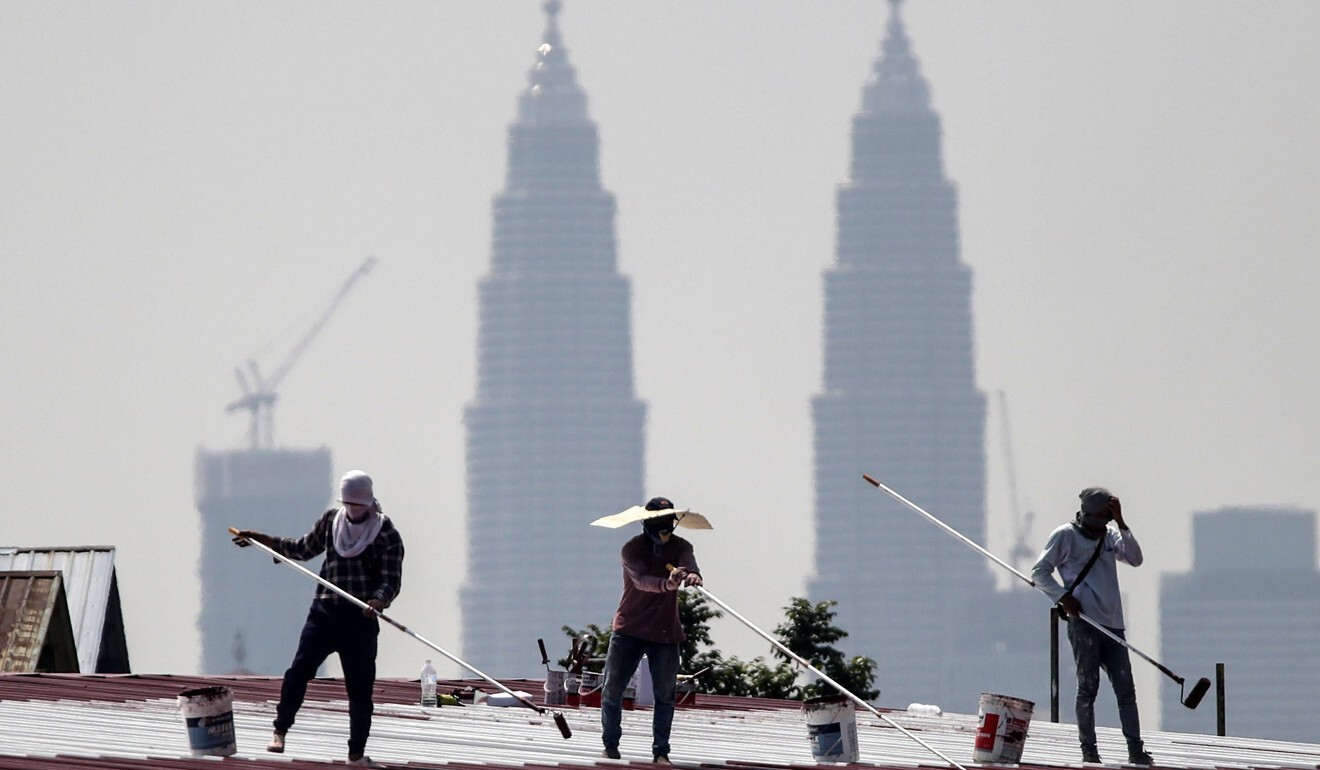 Construction workers paint a factory roof against a background of the Twin Towers of Kuala Lumpur. Photo: EPA