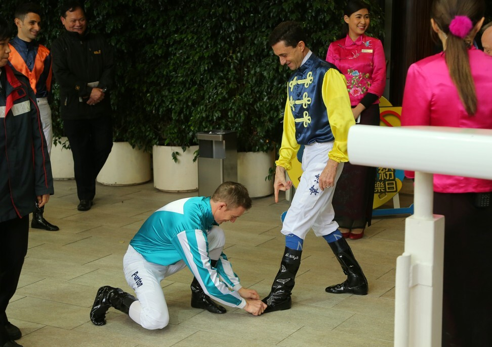 Zac Purton pretends to shine Douglas Whyte's boots on his final day of riding in 2019.