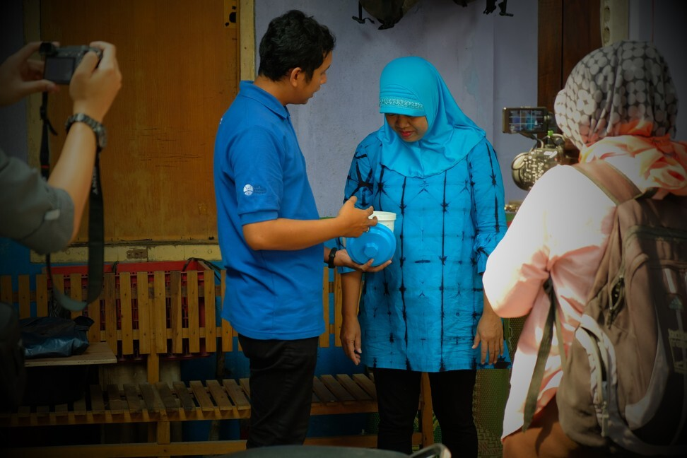 A programme member trains local community members to use mosquito release containers.